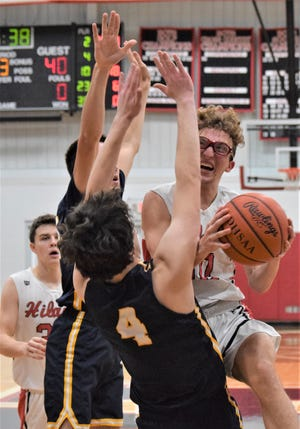 Hiland's Will Schlabach drives hard to the hole despite the defensive effort of Toledo Christian's Joe O'Neil (4) during high school boys basketball action Friday night. The Hawks lost, 63-49.