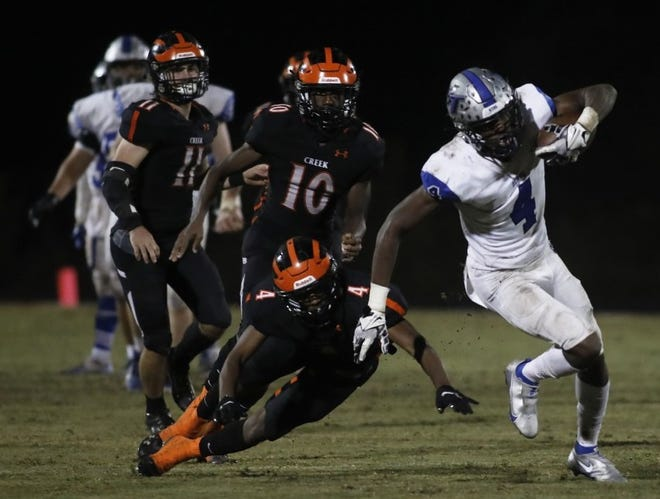 Braylon Fowler (4) slips away from a defender and scores on a 61-yard touchdown pass in the fourth quarter of Bartram Trail's 35-13 playoff win at Spruce Creek. [News-Journal/Nadia Zomorodian]