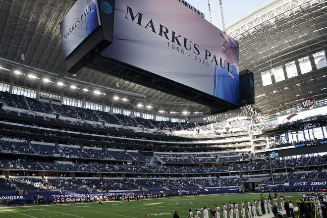 An image of Dallas Cowboys strength and conditioning coordinator Markus Paul is projected on the video screen as all in attendance observe a moment of silence before the Thanksgiving Day game against the Washington Football Team in Arlington, Texas. Paul, a former Syracuse University All-American, died on Wednesday
