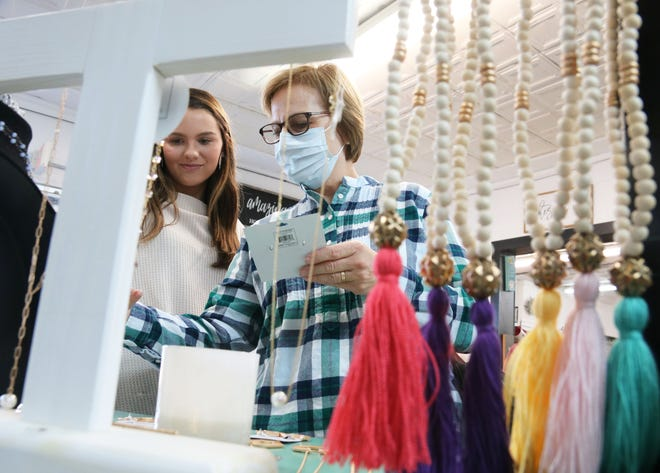 Lynn Whaley, right, looks at jewelry employee Makayla Sasnett shows her at Lovie Jane's Boutique, located at 2609 W. Vernon Ave., on Small Business Saturday.