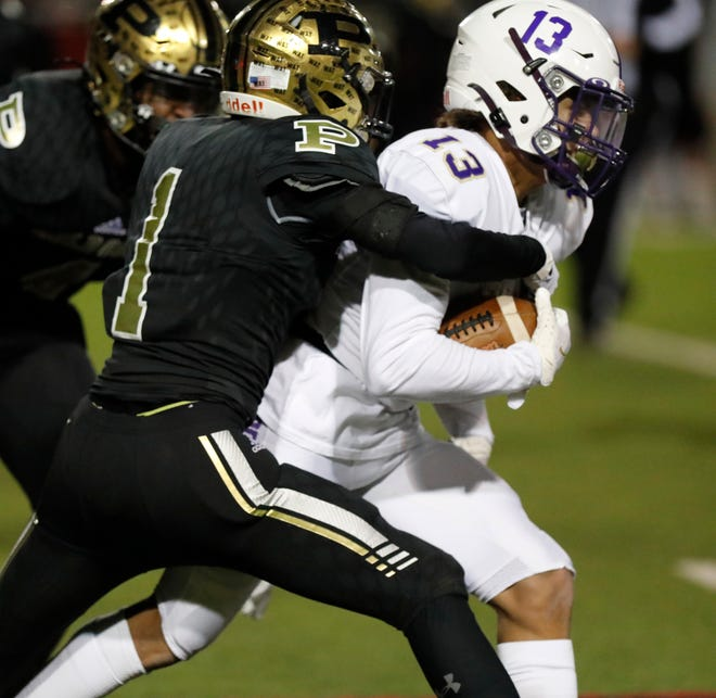Post's Josiah Ward (1) tackles Panhandle's Zion Mercer (13) during the first half of a Class 2A Division I playoff game Nov. 27 at Pirate Stadium at First United Park.
