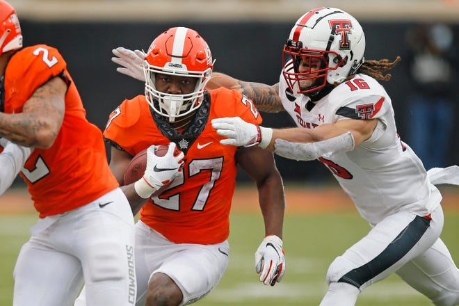 Oklahoma State running back Dezmon Jackson (27) carried 36 times for 235 yards and three touchdowns Saturday during the Cowboys' 50-44 home victory against Texas Tech. Red Raiders safety Thomas Leggett (16) was credited with eight tackles.