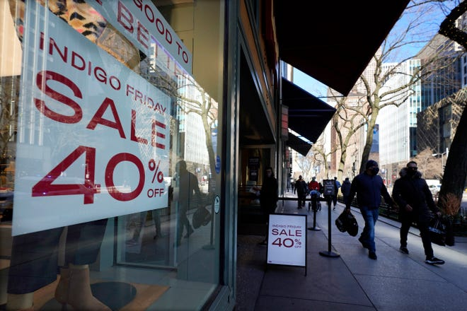 Shoppers pass an Indigo Friday 40% Off sign Saturday on Chicago's famed Magnificent Mile shopping district.