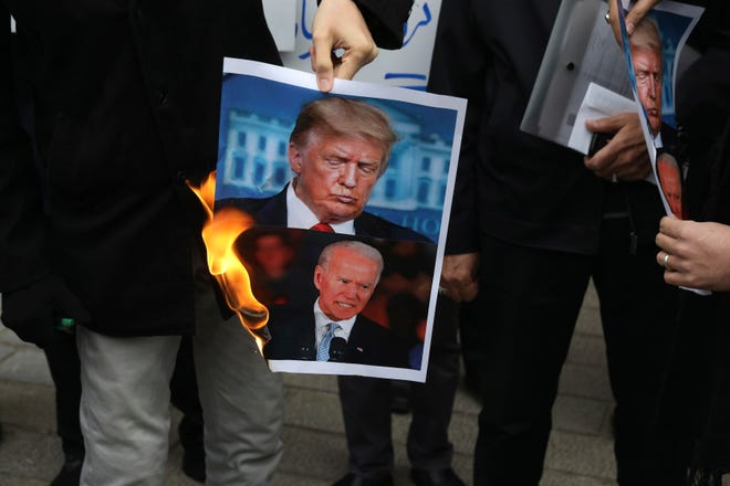 A group of protesters burn pictures of the U.S. President Donald Trump, top, and the President-elect Joe Biden in a gathering in front of Iranian Foreign Ministry on Saturday, a day after the killing of Mohsen Fakhrizadeh an Iranian scientist linked to the country's nuclear program by unknown assailants near Tehran.