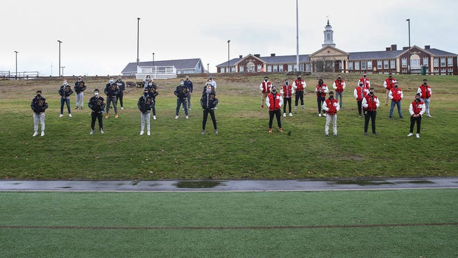 Needham and Wellesley High football players pose for a photo at Needham High's Memorial Field on Nov. 26, 2020. The oldest public school Thanksgiving Day rivalry in the country didn't happen this year due to COVID-19 concerns.