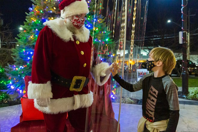 Six-year-old Leo Walker and Santa connect safely Friday night at Commons Park in Canandaigua.
