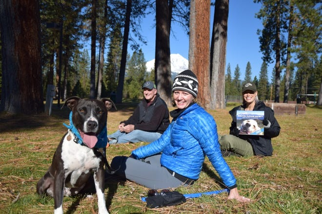 Siskiyou Humane Society McCloud board members, Mark Trent, Linn Tyhurst and Anne-Marie Hosler holding the 2020/2021 pet calendar, sit with Ziggy, an adopted companion from the shelter. Together, they plan on building Siskiyou Humane Society and giving homeless animals a voice and a home.