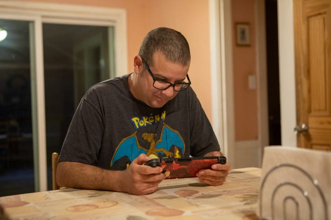 Kevin, from Holbrook, plays Pokémon at the kitchen table at his home on Friday, Nov. 27.