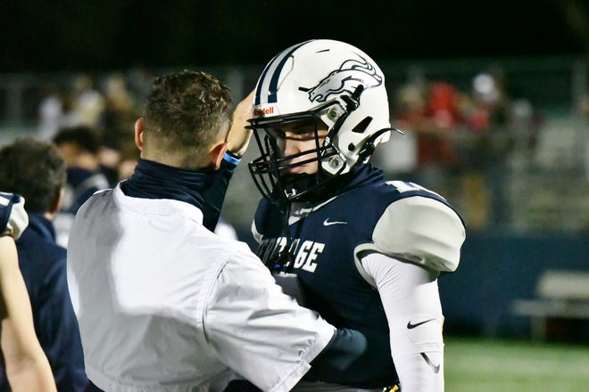 Heritage head coach Nick Martinez and quarterback Dylan Rizk share a moment following Friday's regional finals matchup against Cardinal Gibbons.