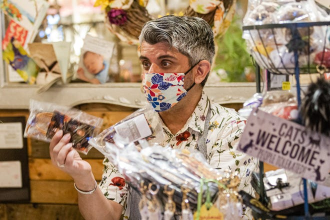 Will Davis, owner of Day by Day Shoppe in Northwood Village, holds up one of the handmade masks he sold at the start of the pandemic. A Northwood Village resident, Davis had to close his shop from March until June 2 because of the coronavirus.
