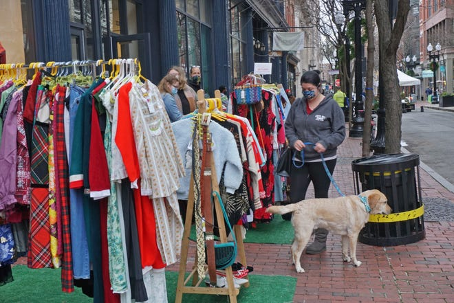 Racks of colorful clothing attract shoppers in front of The Vault during Open Air Saturday in downtown Providence.
