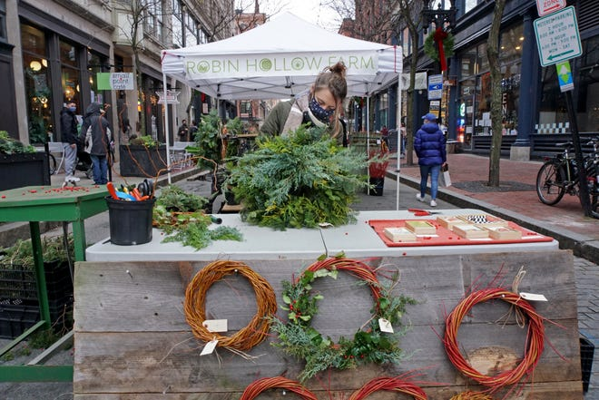 Jenna Lavallee, of Robin Hollow Farms in Saunderstown, makes a wreath during Open Air Saturday in Providence. Each Saturday through Dec. 26 from noon to 6 p.m., Westminster Street will be closed to traffic between Eddy and Mathewson streets, and Union Street will be closed between Weybosset and Westminster so that pedestrians can browse downtown shops outside in the fresh air.