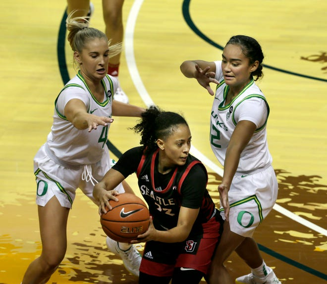 Oregon's Jaz Shelley, left, and Te-Hina Paopao, right, force a turnover against Seattle University's Bree Calhoun during the first quarter of last Saturday's game.