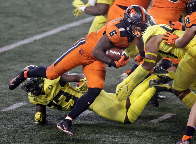 Oregon State's Jermar Jefferson (6) breaks a tackle on his way to one of his two touchdown runs in Friday's 41-38 win over Oregon.