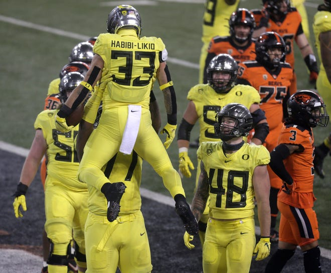Oregon's Cyrus Habibi-Likio (33) is hoisted aloft by teammates after scoring during the fourth quarter of last week's game against Oregon State.
