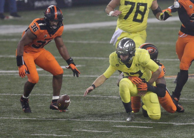 Oregon's Tyler Shough, center, fumbles the ball as the Ducks try to keep the last play alive at the end of the game against Oregon State.