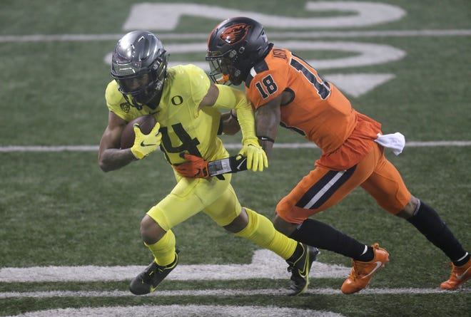 Oregon wide receiver Kris Hutson, left, fights for extra yardage against Oregon State's Alex Austin after catching a pass in the second quarter of last week's game.