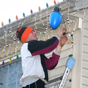 Ivan Sturm hangs another string of lights on his home at 6097 Armistice Ave. NW in Jackson Township. The holiday light display, which features tens of thousands of lights and hundreds of lawn decorations, will be ready to view by the first weekend in December.