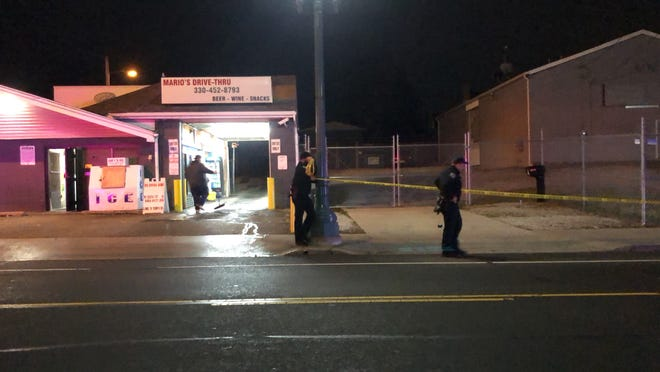 Canton police officers take down yellow crime scene tape by Mario's Drive-Thru at 914 12th St. NE in Canton on Friday night. They referred questions about what happened to a police supervisor who could not later be reached for comment.