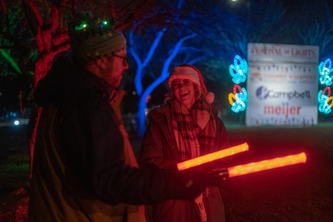 B103 on-air talent Chelsea Meyer, right, laughs while directing traffic at the Festival of Lights in Sinnissippi Park on Nov. 27, 2020, in Rockford.