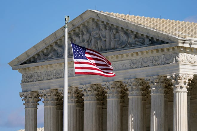 In this Nov. 2  photo an American flag waves in front of the Supreme Court building on Capitol Hill in Washington.