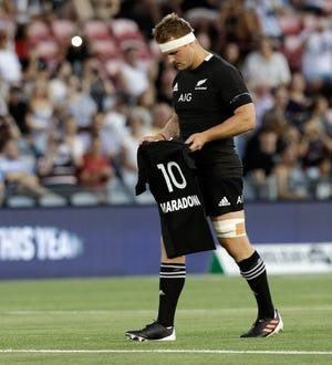 New Zealand captain Sam Cane lays All Black number 10 jersey on the pitch in memory of late Argentina soccer star Diego Maradona prior to the start Tri-Nations rugby test between Argentina and the All Blacks on Saturday.