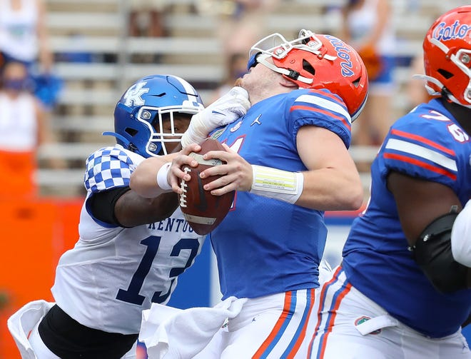 Florida quarterback Kyle Trask is hit in the face by Kentucky linebacker J.J. Weaver during Saturday's game at Ben Hill Griffin Stadium. Weaver drew a personal foul penalty.