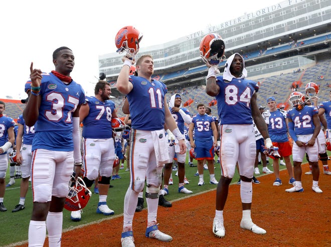 Florida players, including Kyle Trask (11) and Kyle Pitts (84), celebrate with teammates Saturday after the Gators beat the Kentucky Wildcats at Ben Hill Griffin Stadium.