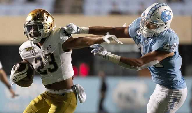 Notre Dame running back Kyren Williams, left, fends off North Carolina linebacker Jeremiah Gemmel in the fourth quarter of Friday's game at Kenan Stadium.