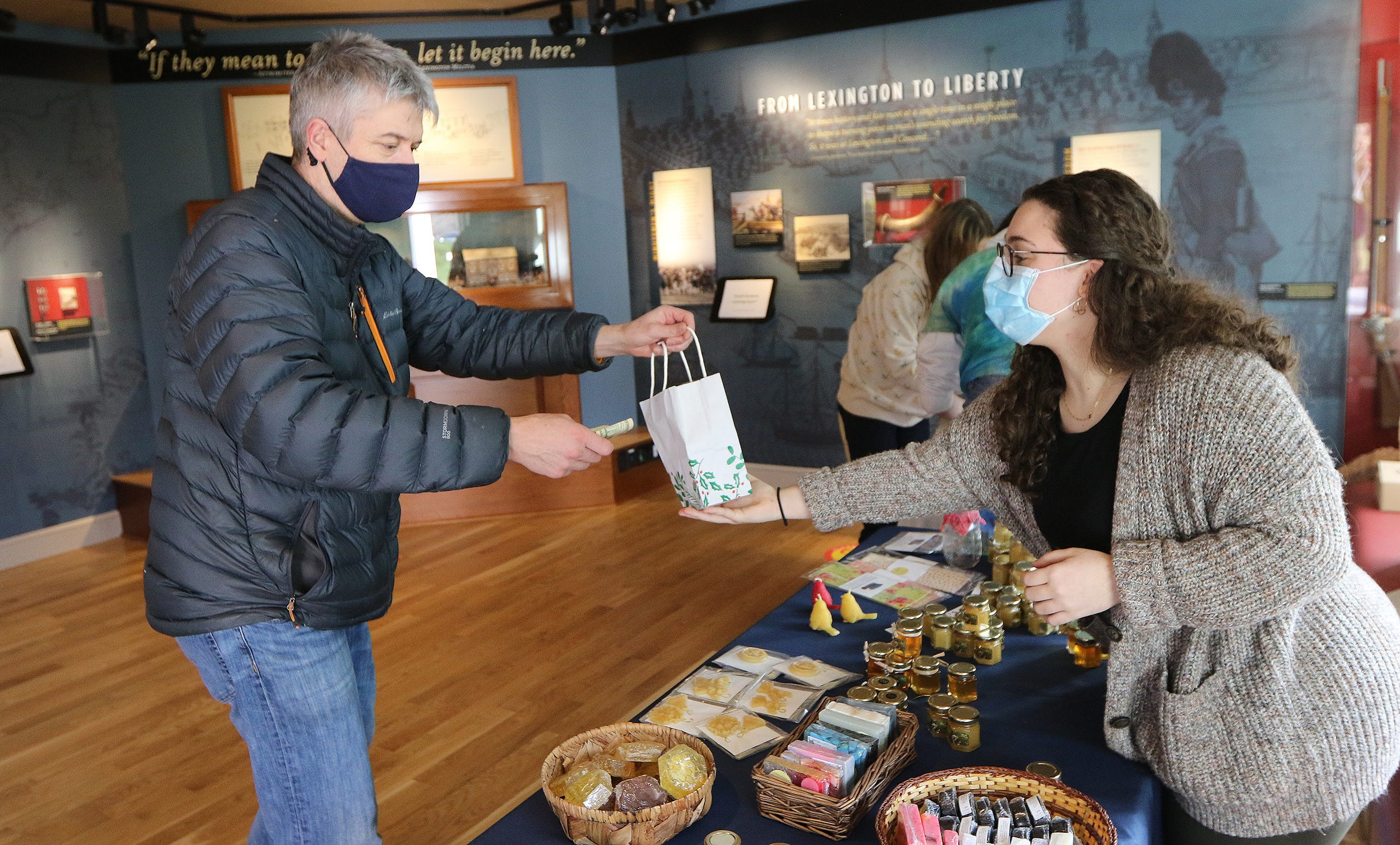 Andy Taggart, of Lexington, bought some items from Lexington High School senior Sophie Gregoretti, 17, at the Lexington Bee Company table in the Lexington Visitors Center, Nov. 28.