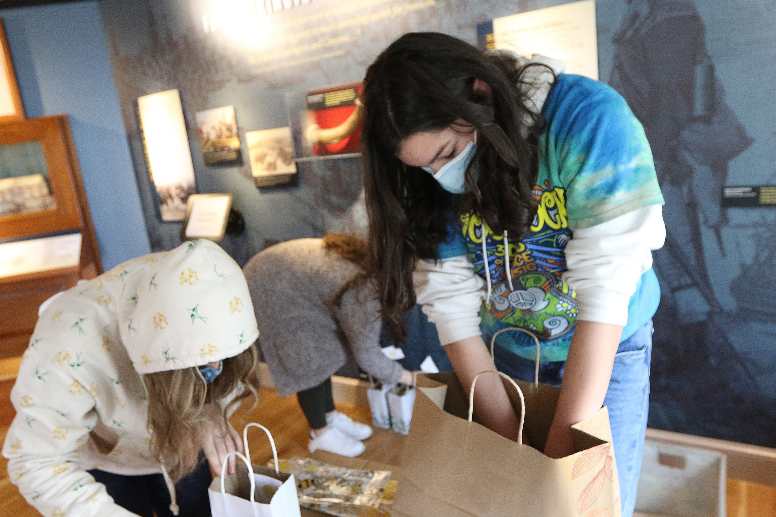 """Freshman Lauren Jolley, 14, and other members of the Lexington High School Beekeepers Association, known also as the """"Bee Club"""", filled advance orders at the Lexington Visitors Center. They were volunteering with the Lexington Bee Company on Small Business Saturday in Lexington, Nov. 28."""