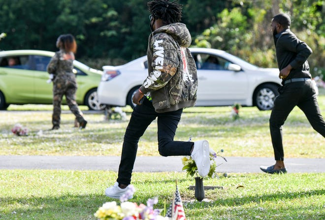 Spectators run from the scene after a shot was fired during a funeral service for Sincere Pierce at Riverview Memorial Gardens in Cocoa, Florida on Saturday, Nov. 27.