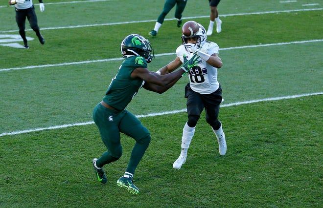 Jayden Reed dari Michigan State, kiri, menangkap umpan di zona akhir untuk touchdown melawan Cameron Ruiz (18) dari Northwestern selama babak pertama.