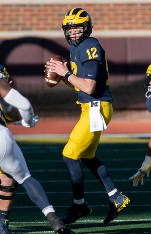 Quarterback Michigan Cade McNamara mencari orang terbuka di kuarter keempat.