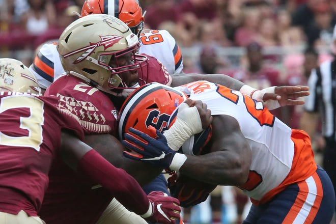 Florida State's Marvin Wilson, left, tackles Syracuse's Jarveon Howard in Tallahassee Fla.