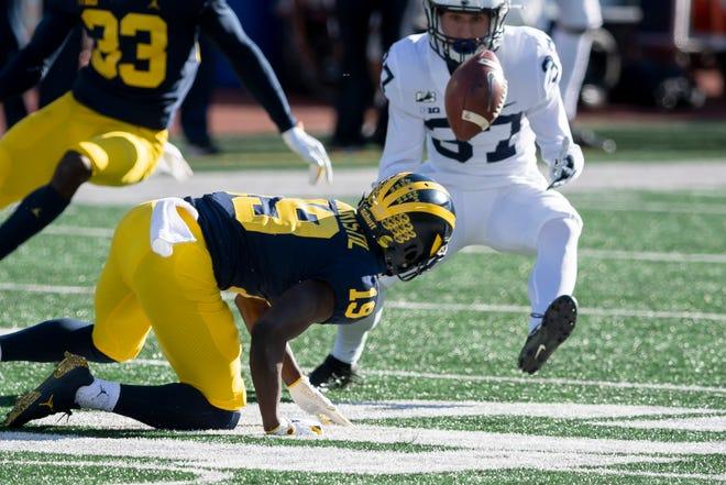 Penerima wide Michigan Mike Sainristil meraba-raba tendangan yang berhasil dipulihkan oleh keselamatan Penn State Drew Hartlaub (37) pada kuarter kedua.