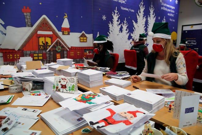 """Pekerja pos yang menyebut diri mereka sendiri """"Peri"""" amplop terbuka dialamatkan """"Uang Natal"""" - Bapak Natal dalam bahasa Prancis - dihiasi dengan hati cinta, stiker, dan kilau, di Libourne, Prancis barat daya, Senin, 23 November 2020."""