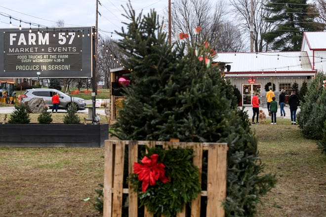 People arrive at Farm 57 in Evansville to look for Christmas trees, Friday evening, Nov. 27, 2020. Farm 57 is open Monday through Friday from 9 a.m. to 7 p.m., Saturdays from 9 a.m. to 6 p.m. and Sundays 10 a.m. to 4 p.m.