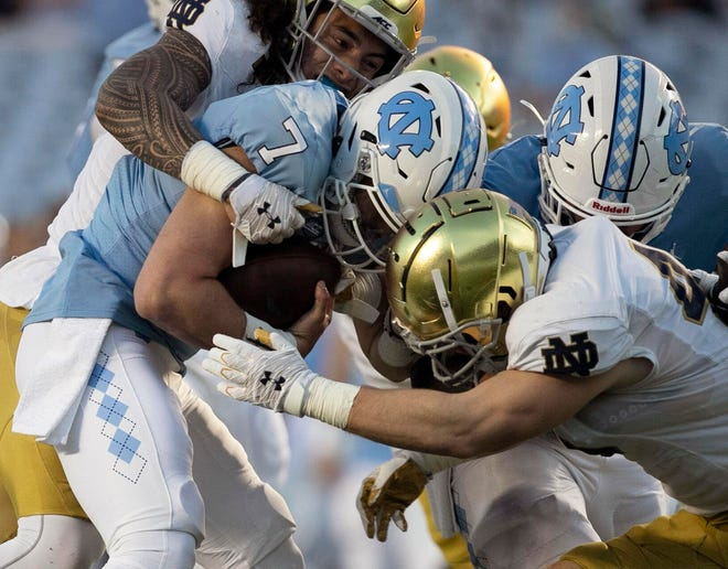 North Carolina quarterback Sam Howell (7) is sacked by Notre Dame's Marist Liufau (35) and Drew White (40)during ND's 31-17 victory Friday at Kenan Stadium in Chapel Hill, N.C.