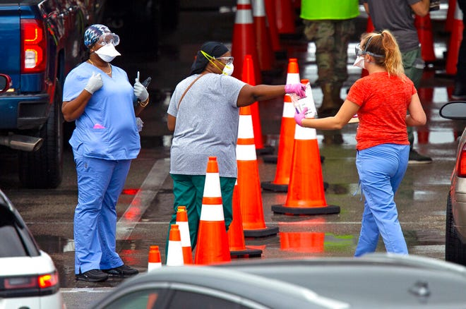 Vehicles line up as a healthcare workers help to check in as citizens is being tested at the COVID-19 drive-thru testing center at Hard Rock Stadium in Miami Gardens on Sunday, November 22, 2020.(David Santiago/Miami Herald via AP)