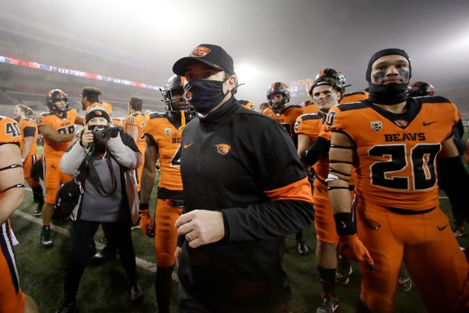 Oregon State Beavers players and head coach Jonathan Smith celebrate the victory On Nov. 27, 2020 against the Oregon Ducks at Reser Stadium in Corvallis, Oregon.