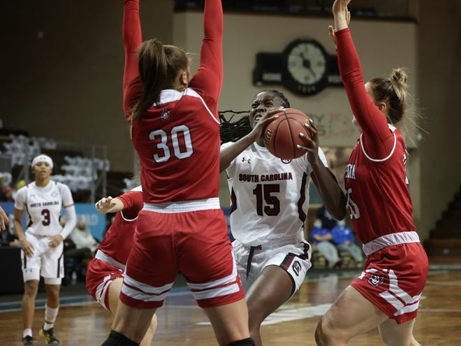 SIOUX FALLS, SD - NOVEMBER 28: Laeticia Amihere #15 of the South Carolina Gamecocks drives toward Jeniah Ugof thesky #30 of the South Dakota Coyotes during the Women's Bad Boy Mowers Crossover Classic at the Sanford Pentagon in Sioux Falls, SD.