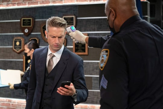 """Detective Sonny Carisi (Peter Scanavin) gets his temperature checked in a Season 22 episode of """"Law and Order: SVU."""""""
