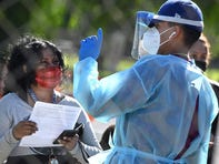 A healthcare worker speaks to a woman at a walk-up Covid-19 testing site, November 24, 2020, in San Fernando, California, just northeast of the city of Los Angeles.  California shattered the state's single-day COVID-19 record with over 20,500 new cases recorded on November 23 ahead of the Thanksgiving holiday.