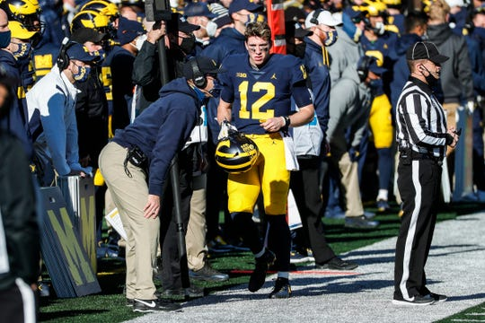 Michigan quarterback Cade McNamara talks to coach Jim Harbaugh during the first half against Penn State at Michigan Stadium in Ann Arbor, Saturday, Nov. 28, 2020.