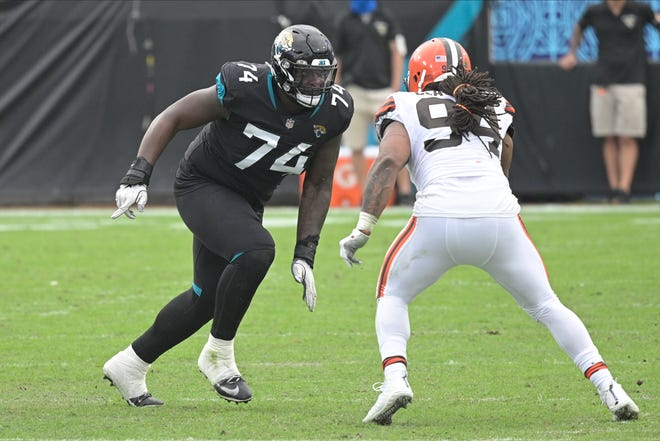 Jacksonville Jaguars offensive tackle Cam Robinson (74) looks to block Cleveland Browns defensive end Adrian Clayborn (94) during the first half of an NFL football game, Sunday, Nov. 29, 2020, in Jacksonville, Fla. (AP Photo/Phelan M. Ebenhack)