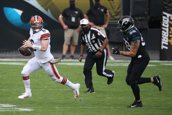 Browns quarterback Baker Mayfield scrambles as Jacksonville Jaguars defensive end Aaron Lynch (59) gives chase during the first half of the Browns' 27-25 win Sunday in Jacksonville. [Stephen B. Morton/Associated Press]
