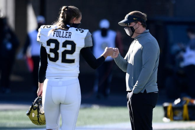 Vanderbilt place kicker Sarah Fuller (32) gets a fist bump from Missouri head coach Eli Drinkwitz after warming up before the start of a game Saturday at Faurot Field.
