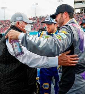 Team owner Rick Hendrick, left, gets a hug from seven-time NASCAR champ Jimmie Johnson with Chase Elliott, who won the Cup title this year, looking on.