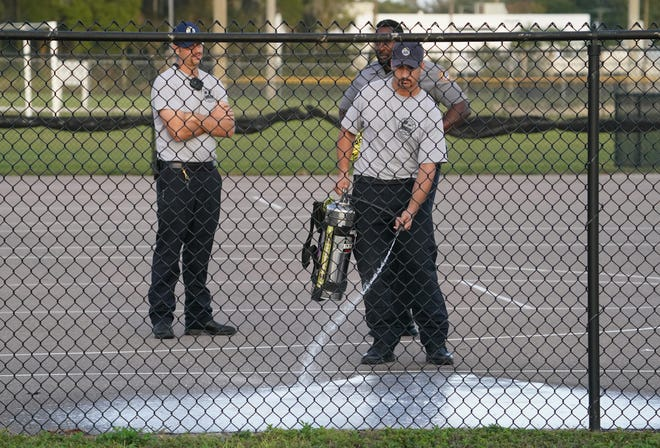 Daytona Beach Fire Department personnel wash down the scene of a deadly shooting at the Derbyshire Park basketball courts in Daytona Beach on Nov. 29, 2020.